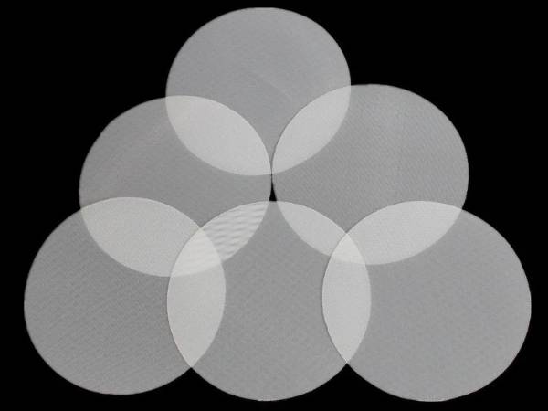 Several pieces of nylon mesh filter discs on black background.