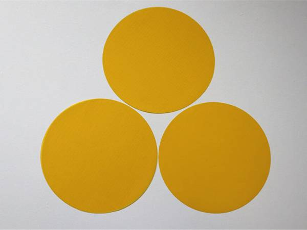 Three pieces of yellow color polyester filter disc on gray background.