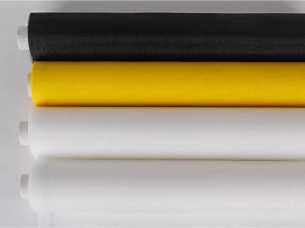 Four rolls of polyester filter mesh fabric in white, yellow and black color.