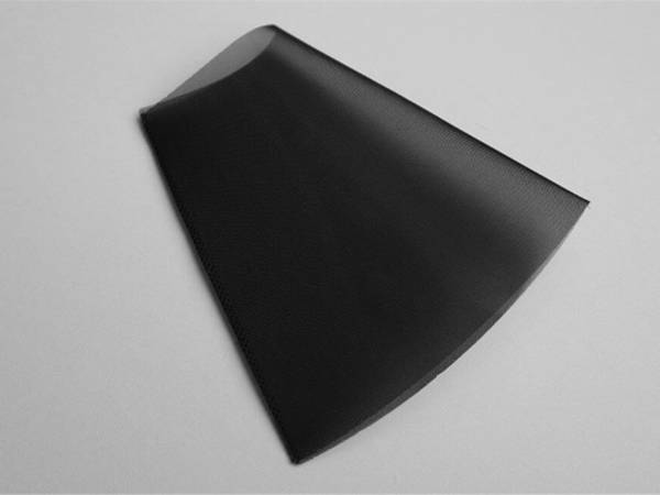 A piece of black color polyester filter tube on gray background.