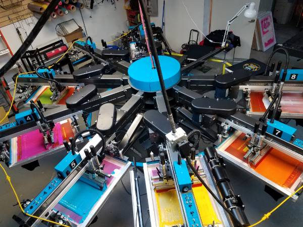 A rotary screen printing machine is printing T-shirts.