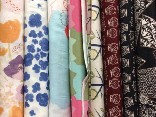 Several different styles of screen printed heavy textile fabrics on the table.