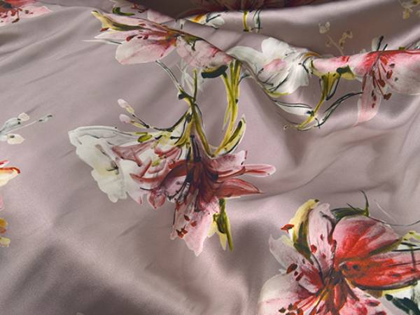 A piece of silk fabric on the table withe beautiful flower pattern on it.
