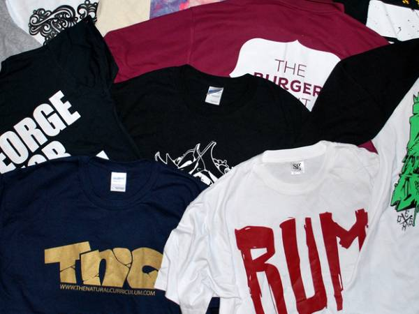 Several different styles of screen printed t-shirts on the table.