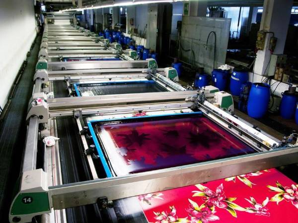 A rotary screen printing machine is printing heavy textile fabrics.